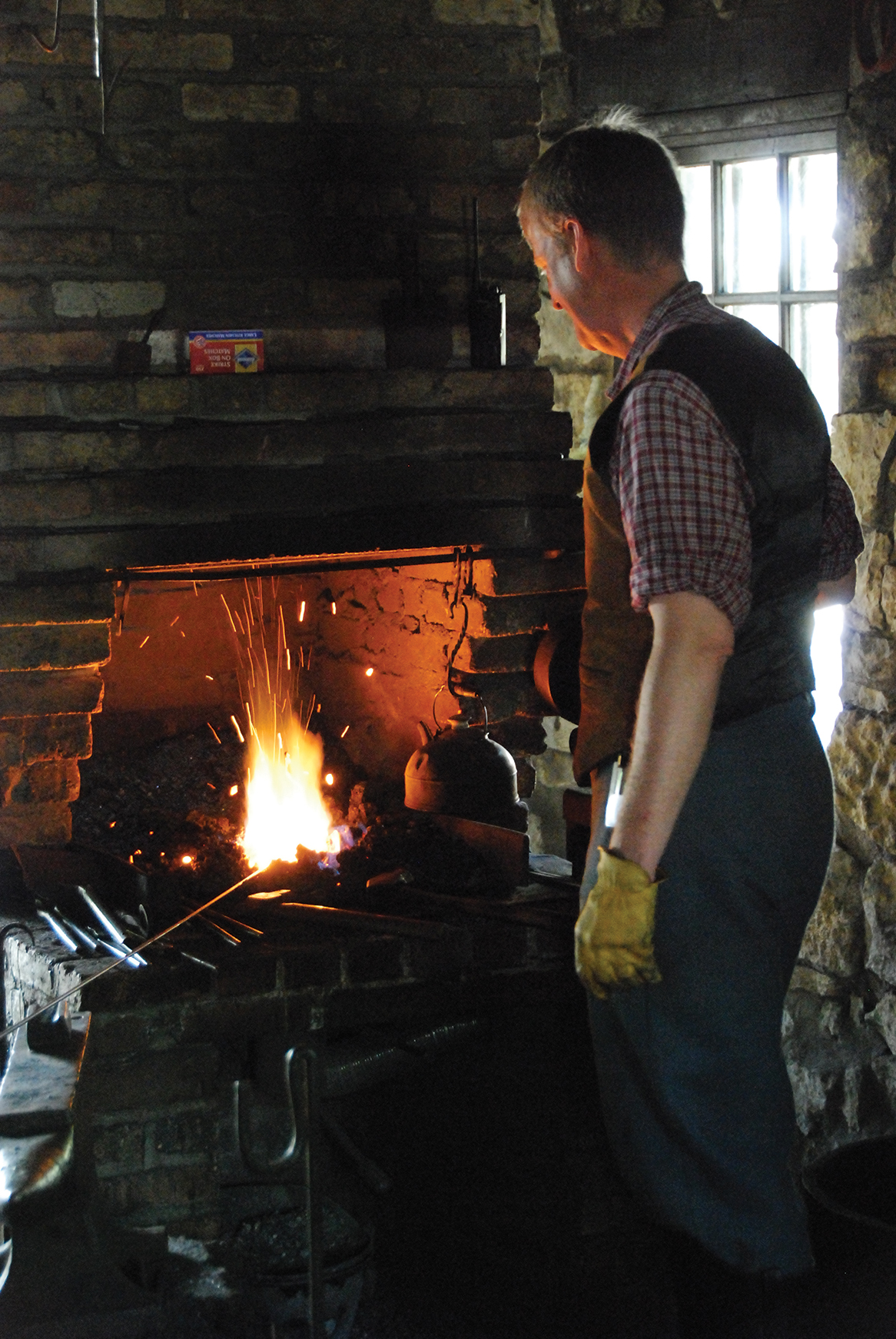 Blacksmith working at forge in Blacksmith Shop